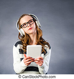 Cute girl with head phones holding tablet. - Close up...