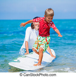Boy with surf - Little boy with his mother learning surfing