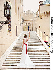 Beautiful young bride outside the castle standing on stairs