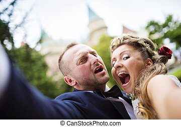 Young wedding couple taking a selfie of themselves as they...