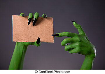 Green monster hands with black long nails pointing on blank...