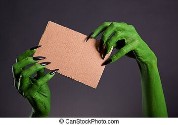 Green hands with long black nails holding empty piece of...