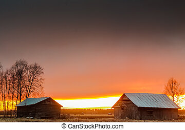 Last Rays Of Sun Behind The Barn Houses - The sunset of a...