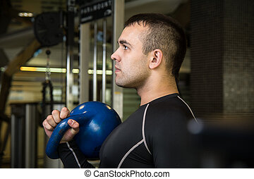 Kettlebell swing workout training man at gym.