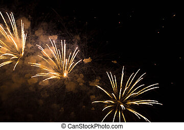 three yellow fireworks in the night sky - three beautiful...