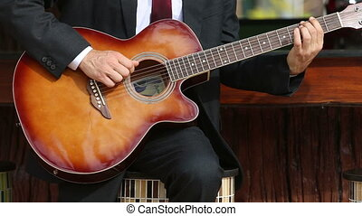 bearded musician in suit and white shirt plays guitar sitting at bar board