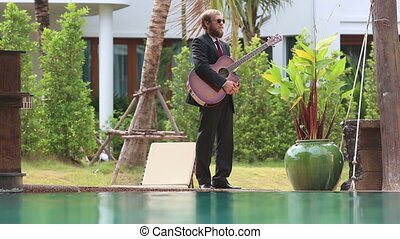 bearded man with guitar looks around at pool - light haired...