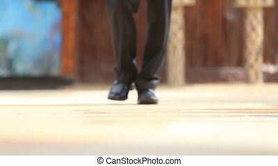man in black trousers and shoes goes ahead