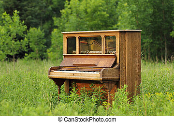 Old Upright Piano Seen Abandoned in a Green Field - Old...