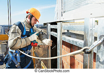 Worker builder at facade installation work - worker builder...