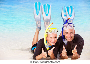 Joyful diver couple lying down on the beach, wearing mask...