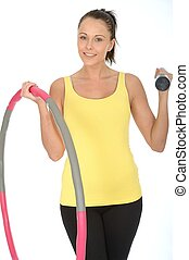 Healthy Young Woman Holding a Dumb Bell and Hula Hoop...