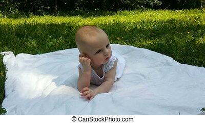 little girl lies on a white cover on a green grass in a...