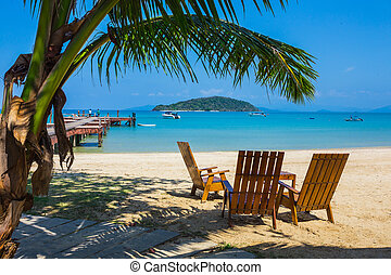 Tropical beach panorama with deckchairs, boats and palm tree...