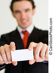 businessman with card - a young businessman holding up his...