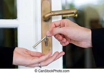 house sold concept - a man handing over a house key to a...