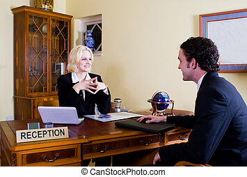 hotel receptionist and customer - a female hotel...
