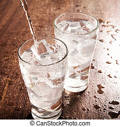 Drinking water is poured into a glass.