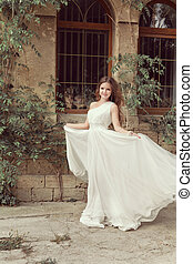 Beautiful young bride girl in wedding dress with blowing...