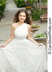 Attractive bride with long wavy hair in wedding dress with...