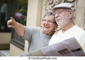 Tourist Senior Couple Looking at Brochure Map - Happy...