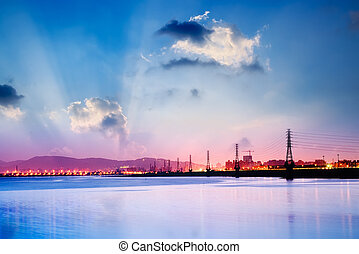 Sunrise cityscape of power tower with beautiful clouds.