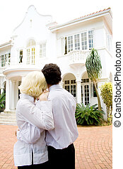 couple dream home - a couple standing outside their new...