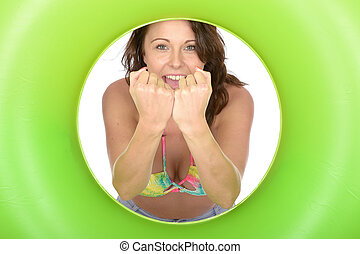 Attractive Young Woman Looking Through a Green Rubber Ring...