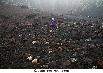 Child standing in spiritual spiral in Etna volcano crater -...