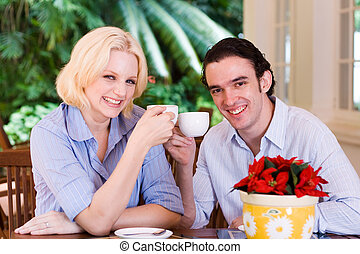 couple - a young couple drinking coffee on outdoor patio