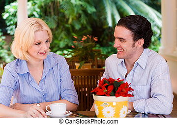 date - a young couple on a date having coffee outdoors