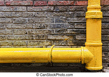 Drain Pipe - Yellow drain pipe of an old building on brick...
