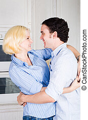 hugging couple - a couple hugging in the kitchen