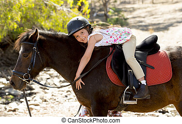 sweet young girl hugging pony horse smiling happy wearing...