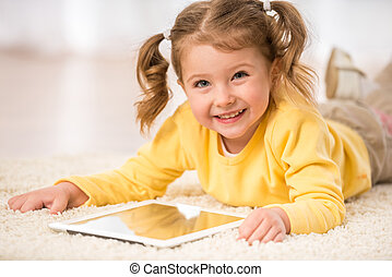 Little girl - Adorable little girl playing with tablet,...