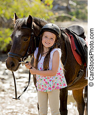 young girl 7 or 8 years old holding bridle of little pony...