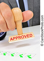man with a rubber stamp with the word approved - a young...