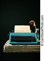old typewriter and a wilted red rose - an old blue...