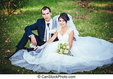 Young couple kissing in wedding gown. Bride holding bouquet...