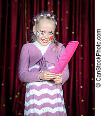 Girl Wearing Clown Make Up Holding Over Sized Comb - Young...