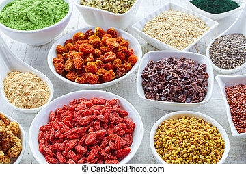 Superfoods - White bowls of various superfoods on white...
