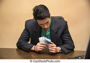Sitting Young Businessman Counting Cash on Hand - Close up...