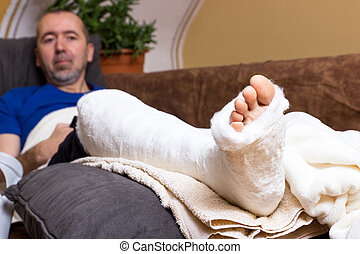 Leg in plaster - A man lying with a broken foot on the sofa...