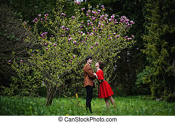 Young beautiful couple in the garden magnolia
