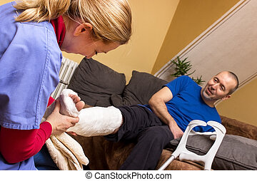 Help at home - A nurse helps a man with a broken leg