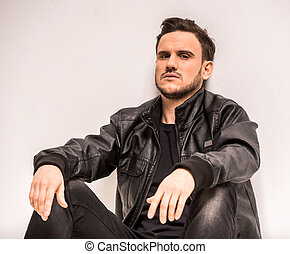 Young man - Young, serious man in leather jacket is sitting...