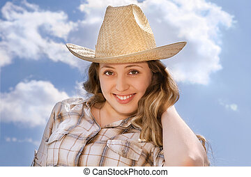 beautiful young woman with cowboy hat at sunny sky background
