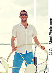 young man in sunglasses steering wheel on yacht - vacation,...
