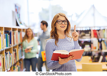 happy student girl or woman with book in library - people,...