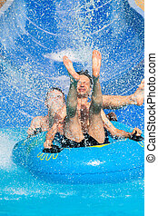 People water slide at aqua park - Two men having fun, people...